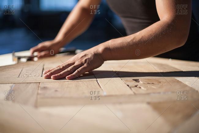 Carpenter piecing together wood pieces in factory, Jiangsu, China
