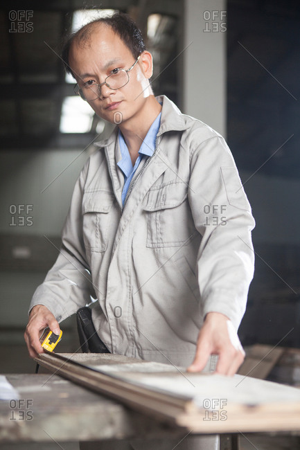 Carpenter measuring length of wood plank with tape measure in factory, Jiangsu, China