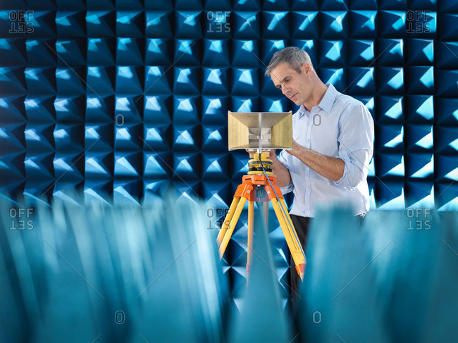 Scientist preparing to measure electromagnetic waves in anechoic chamber