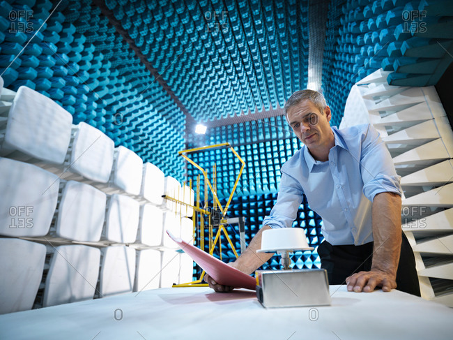 Scientist preparing to measure electromagnetic waves in anechoic chamber, low angle view