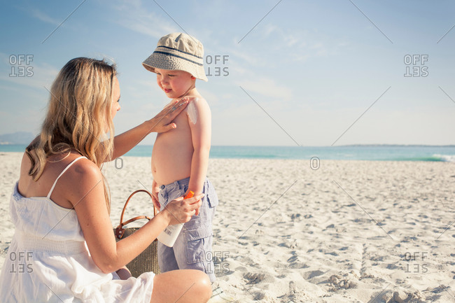 Mid adult mother applying sun lotion to young son on beach, Cape Town, Western Cape, South Africa
