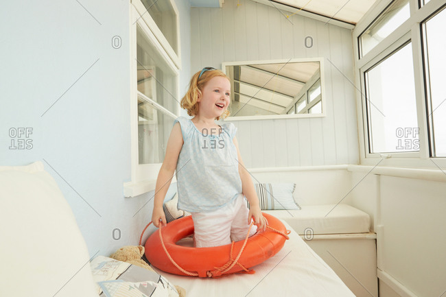 Girl playing with life belt on vacation apartment seat