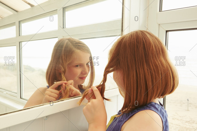 Girl plaiting hair in vacation apartment porch