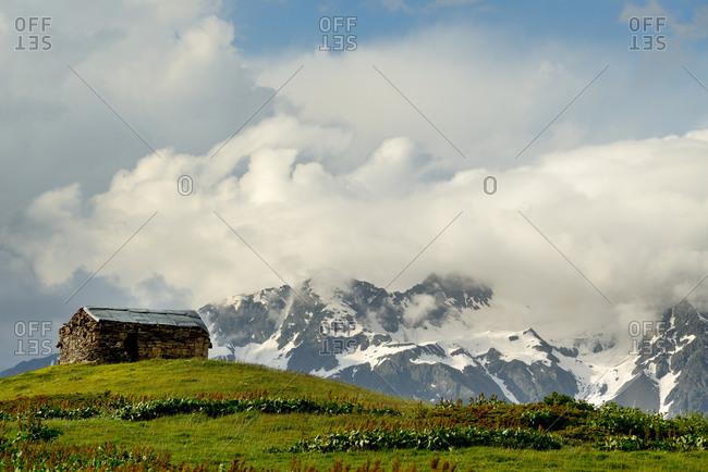 Barn on hill and distant mountains, Mazeri village, Svaneti, Georgia