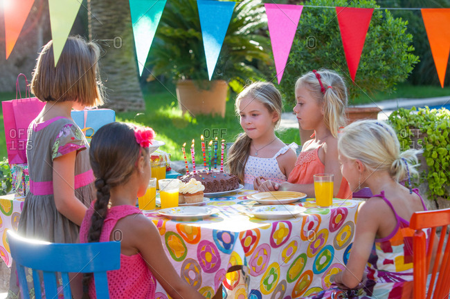 Girl with friends at table with birthday cake