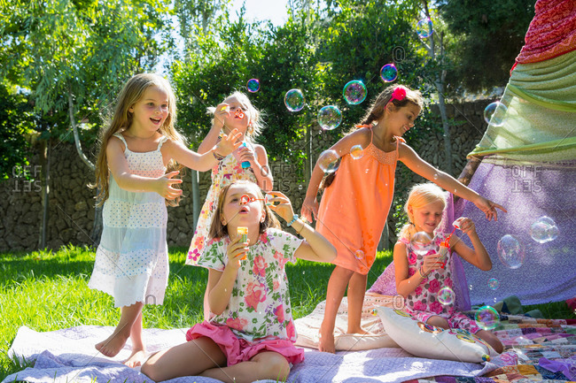 Girls blowing bubbles in summer garden party