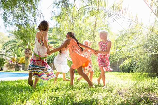 Five girls playing ring a ring a roses in garden