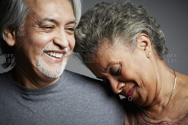 Portrait of a smiling middle-aged couple on a gray seamless background