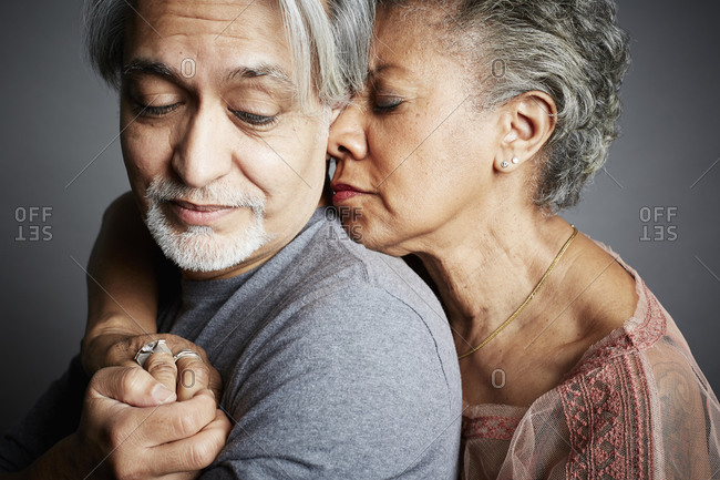 Portrait of a middle-aged couple hugging on a gray seamless background