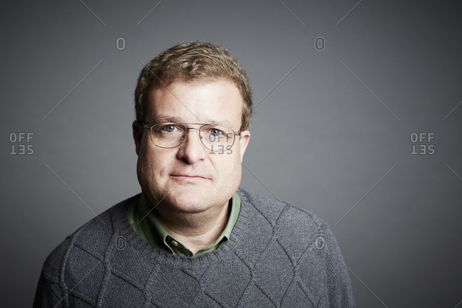 Portrait of a man wearing eyeglasses and a sweater on a gray seamless background