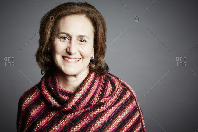 Portrait of a middle-aged woman wearing a cowl neck sweater on a gray seamless background
