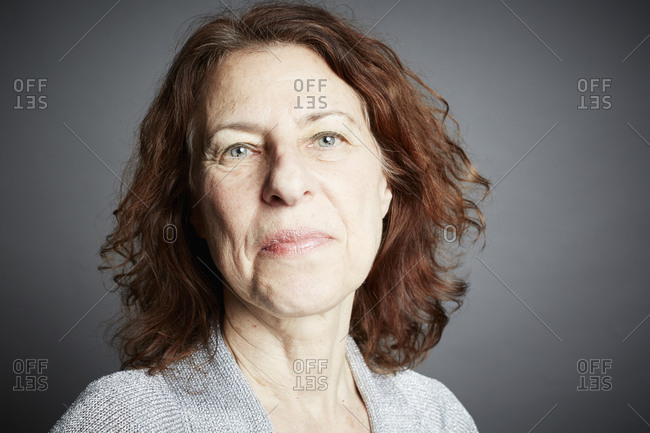 Portrait of a middle-aged woman on a gray seamless background