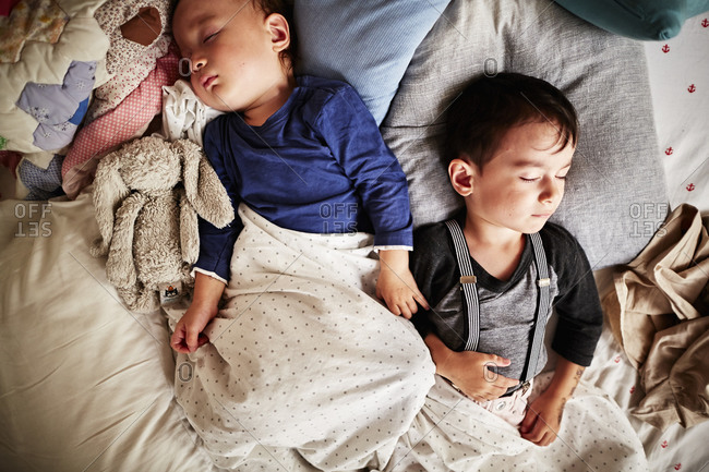 Two young boys asleep in bed