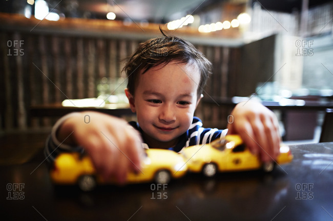 Boy playing with toy taxi cabs