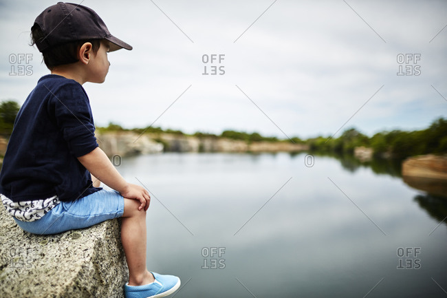 Boy sitting on a rock overlooking a placid lake