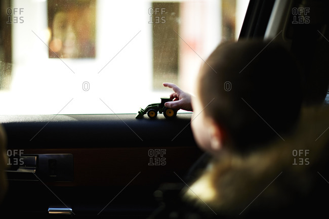 Boy sitting in a car playing with a toy tractor