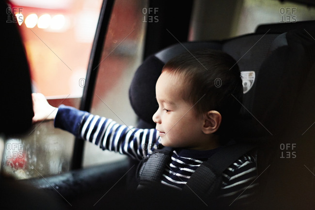 Boy sitting in a car with his hand on the window