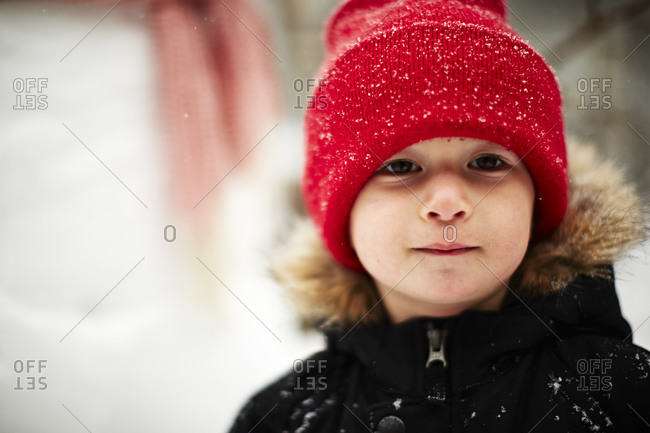 Boy wearing a red knit hat and a winter coat standing outside in the snow