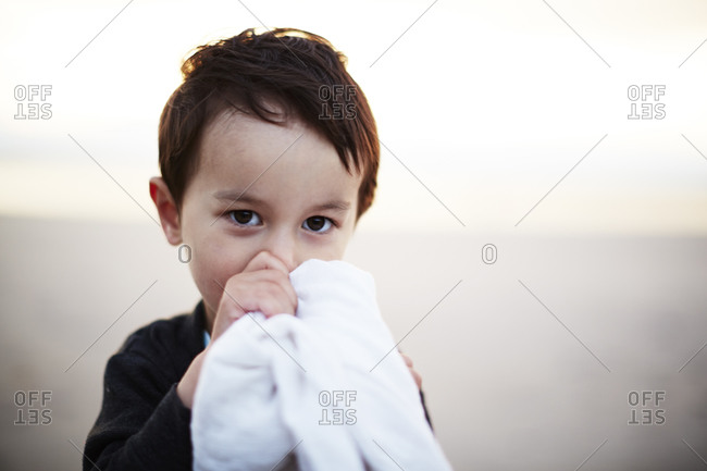 Boy holding a blanket and sucking his thumb outside