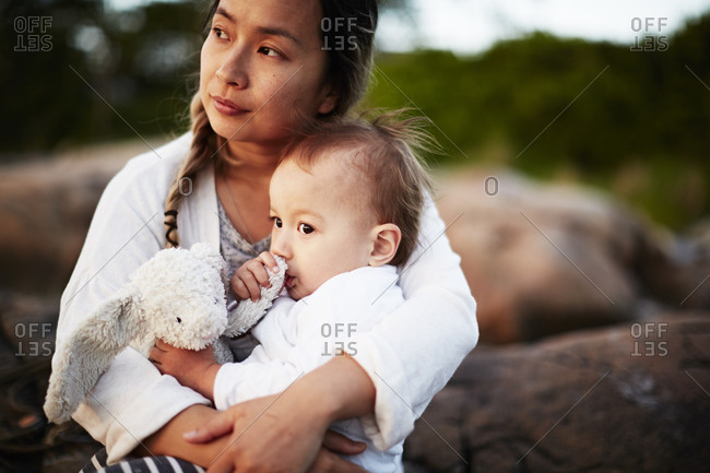 Mother holding her child outside at sunset