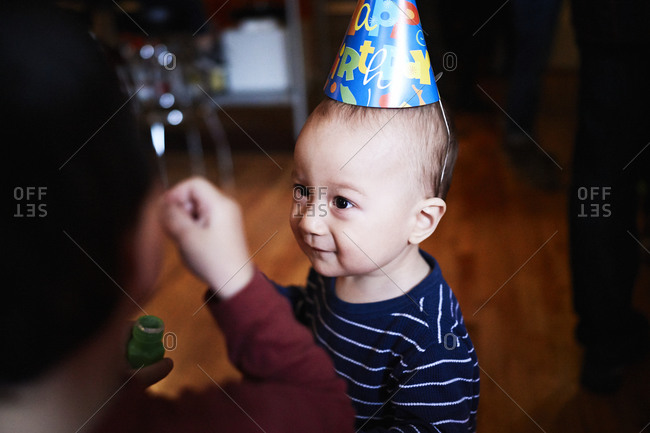 Young boy wearing a birthday party hat