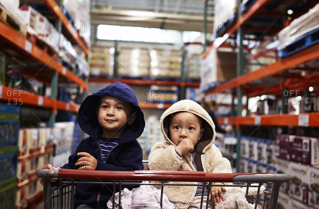 Two young boys sitting side-by-side in a cart in a store