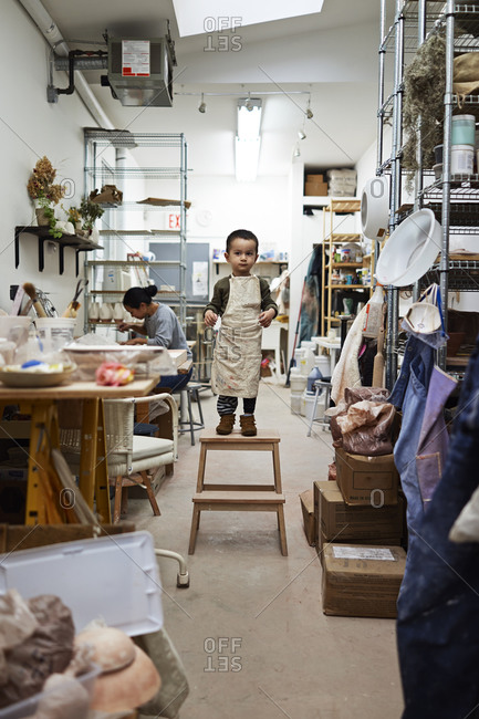 Young boy standing on a stool in a crafting studio