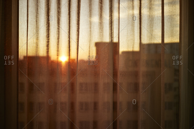 City skyline visible through sheer curtains