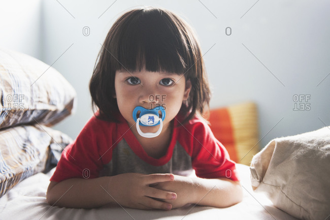 Young boy on a bed with a pacifier