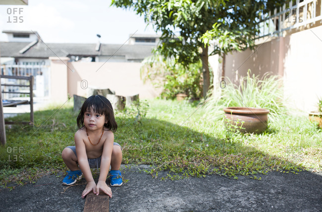Young boy squatting outside in the yard