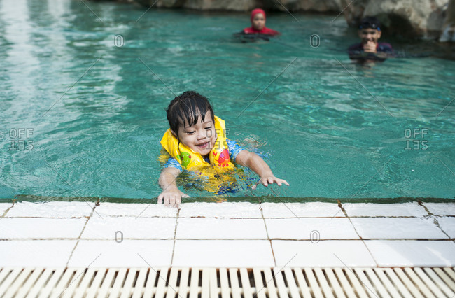 Young boy wearing a flotation device practicing swimming in a pool