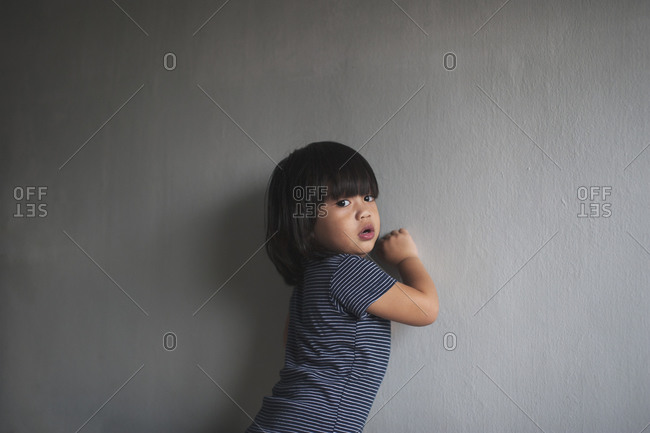 Young boy in a striped onesie standing against a wall