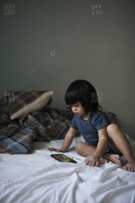 Young boy sitting on a bed with a digital tablet