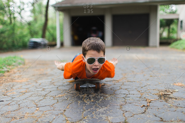 Boy wearing sunglasses riding a skateboard lying down
