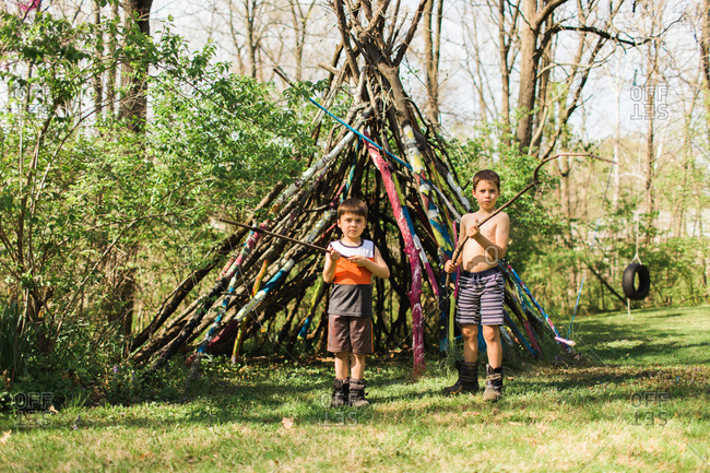 Two boys holding sticks and standing in front of a teepee
