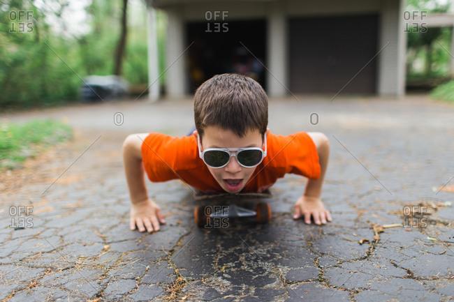 Boy wearing sunglasses riding a skateboard lying down