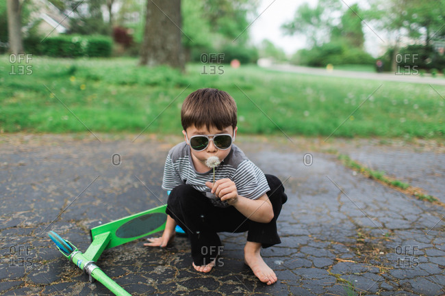 Boy wearing sunglasses blows on a dandelion while kneeling next to his scooter