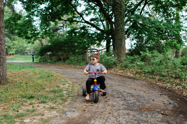 Boy wearing sunglasses riding a tricycle down a path