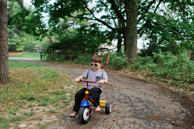 Boy wearing sunglasses riding a tricycle down a tree lined path