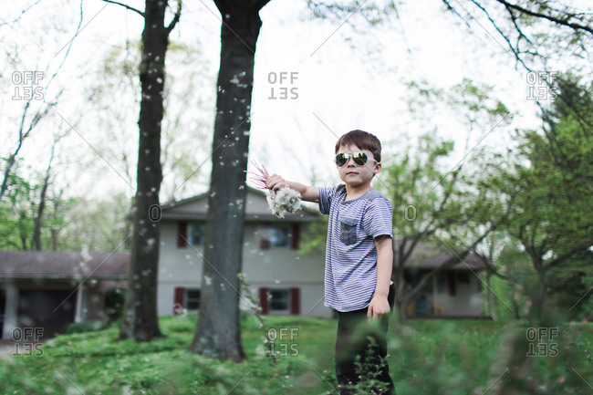 Boy wearing sunglasses waving dandelions in the air