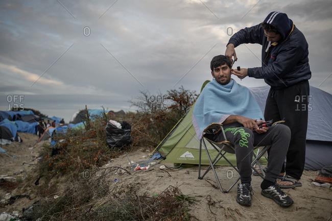 Calais, France - November 3, 2015: Man getting a haircut at refugee camp in Calais, France