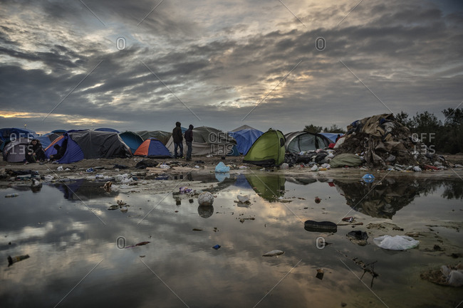 Calais, France - November 3, 2015: Tents and garbage reflected in puddle at migrant camp in Calais, France
