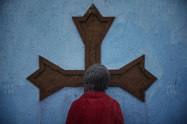 Person standing in front of cross on wall at makeshift migrant camp, Calais, France