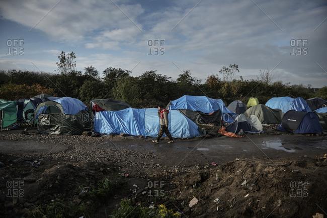 Calais, France - November 4, 2015: Man walks along muddy road at camp for refugees in Calais, France