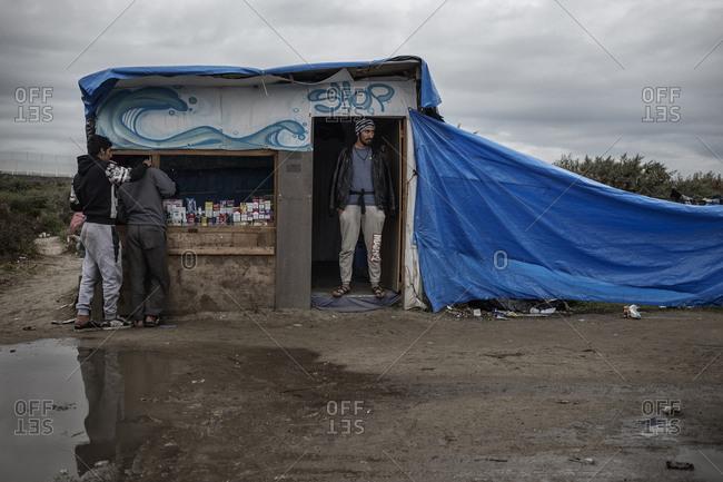 Calais, France - November 5, 2015: Man working at makeshift supply store at Calais migrant camp, France