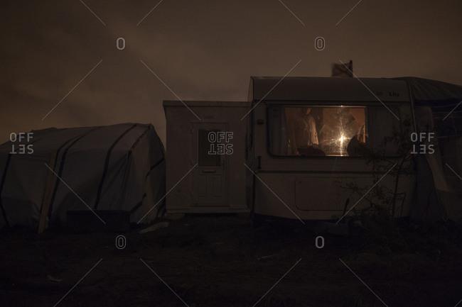 People inside a camper at night at refugee camp, France