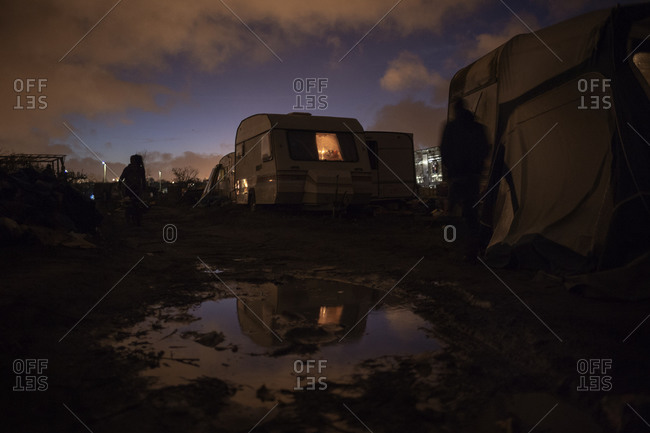 Campers in the mud at sundown, Calais, France