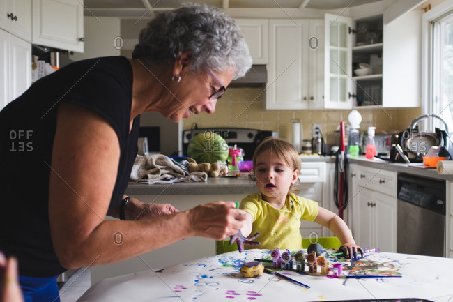 Grandmother helping a child paint at the kitchen table