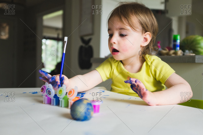 Little girl painting at the kitchen table