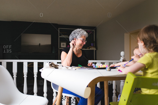 Woman helping a child paint at the kitchen table